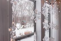 snowflake Christmas lights and snowy scene out a window