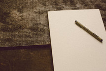 Blank piece of paper and a pen on a wooden table.