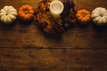 Pumpkins and a candle on a wooden table -- fall decor.