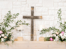 cross and flowers on an altar at a wedding