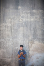 man reading a Bible in front of a gray wall with graffiti