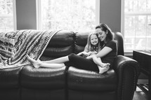 a mother and daughter snuggling on a couch