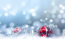 Red and silver Christmas decorations with blue bokeh background