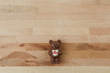 A chocolate bear holding a Valentine heart on a wooden background.