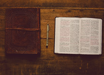 Open Bible, leather journal and a pen on a wooden table.