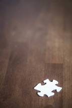 white puzzle piece on a wood table
