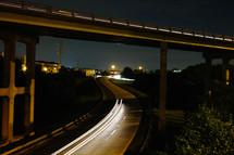 A night scene of a highway under an overpass lit by headlights.
