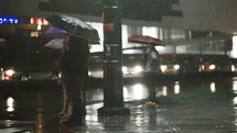 people with umbrellas standing in the rain at night