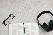 reading glasses, headphones, and open Bible
