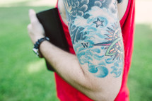 man with tattoos holding a Bible