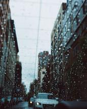 rain on a rear window in a car in traffic