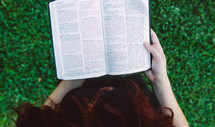 woman reading a Bible in the grass