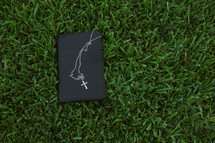 Bible and cross necklace in the grass