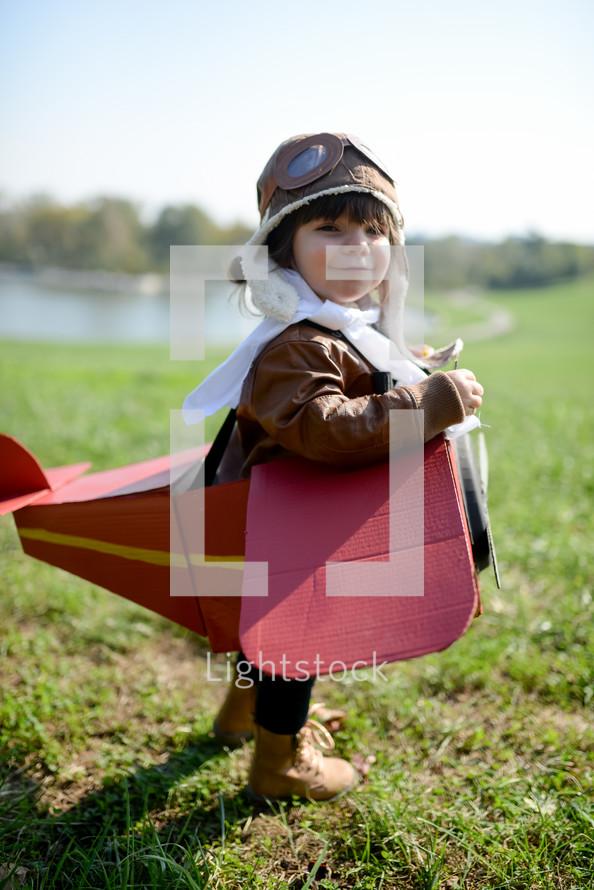a child in a cardboard box airplane