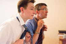 father and son putting on neckties
