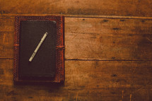 A leather journal, Bible, and a pen stacked on a wooden table.