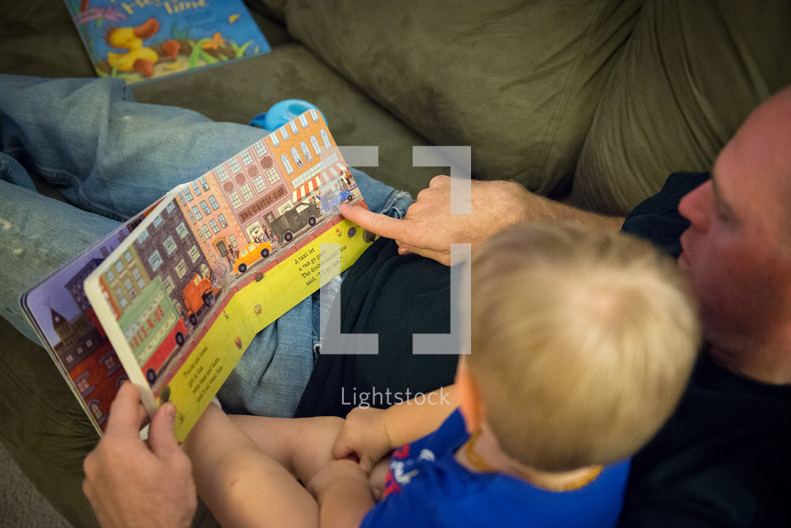 father and toddler son reading a book