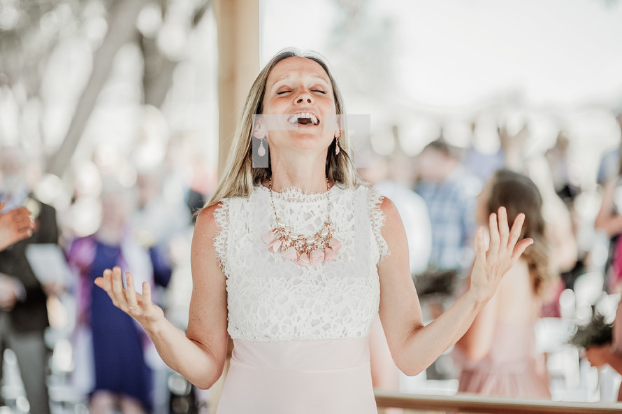 a bride with hands raised praising God
