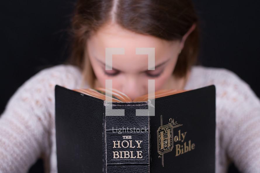 Girl praying behind a Bible.