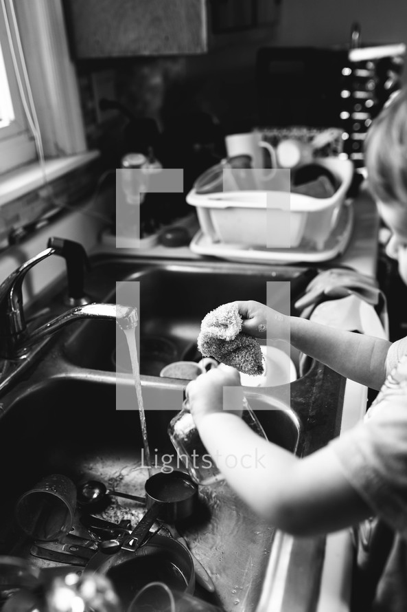 child washing dishes in the sink