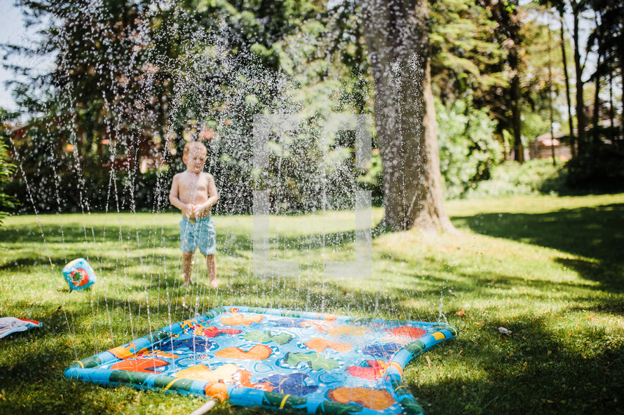 child playing in a sprinkler