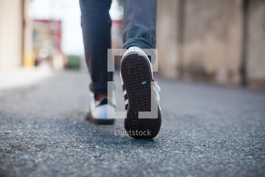 man walking down an alley