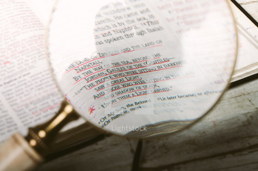 Magnifying glass over pages of Bible open to Matthew 4:15 laying on wooden table.