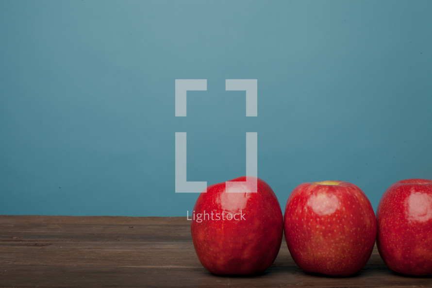 Three red apples lined up on a wooden surface with a blue background.