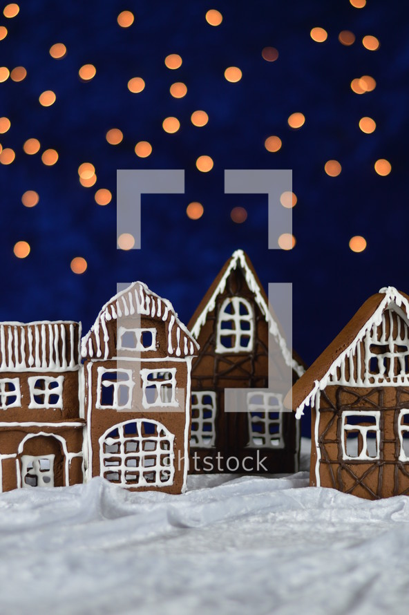 home made delicious sweet traditional gingerbread town with bokeh sky out of blue velvet and christmas lights as advent decoration