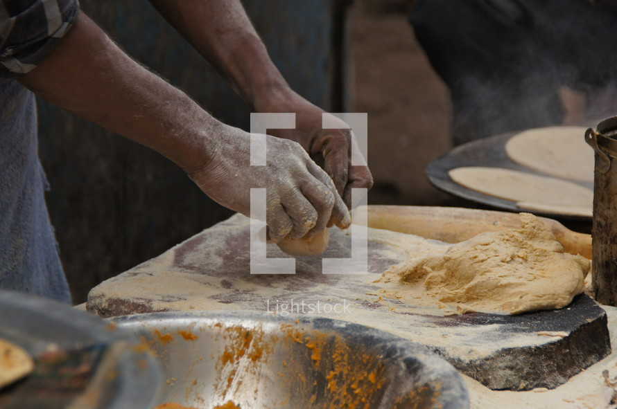 Man kneading dough in an indian bakery