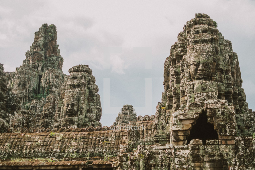 faces carved in stone in the ruins of a temple in Cambodia