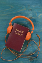 bible with orange headphones on teal wooden background
