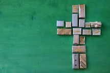 many little presents shaping a cross on green wooden background