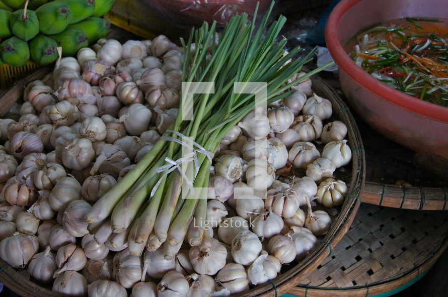 Green onions in a basket of garden cloves. Bananas in the background.