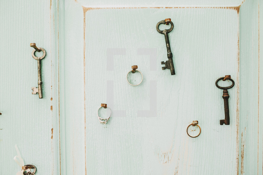 keys and wedding rings hanging on a wall