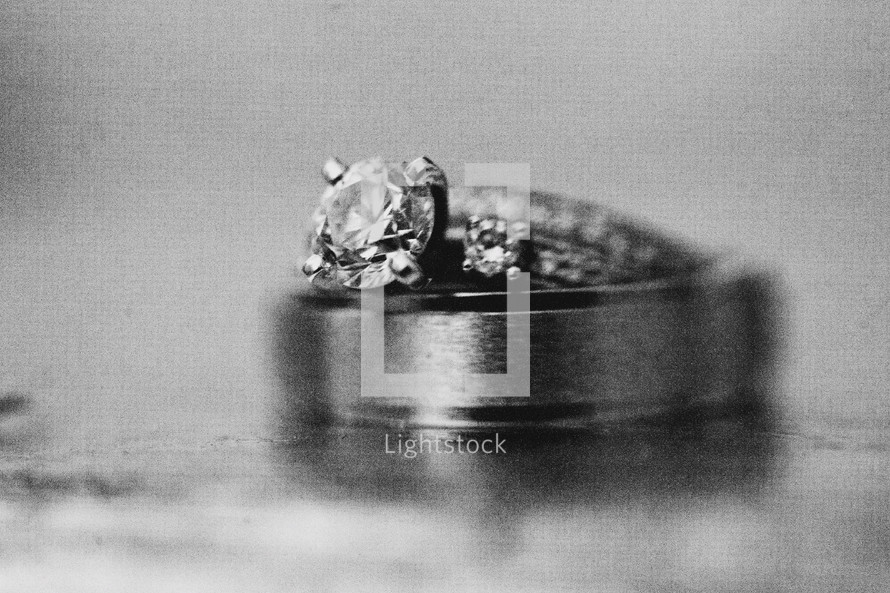 Engagement ring and wedding band sittng on top of solid surface.