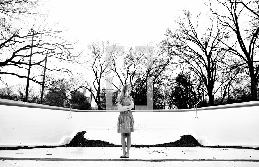 Girl standing in empty swimming pool