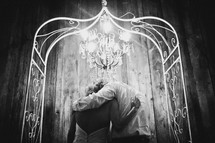 bride and groom under a chandelier and arbor