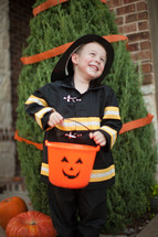 a boy child in a fire fighter costume trick-or-treating on Halloween