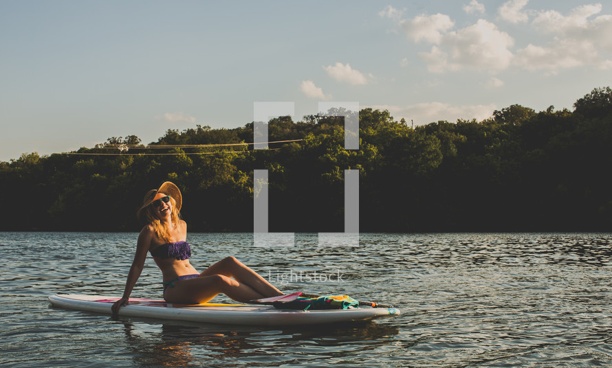woman sitting on a paddle board
