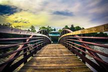 wood bridge and gazebo over a lake