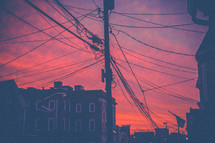 power lines and glow of a pink sky in a city
