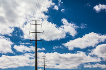 power lines and power pole with clouds in a blue sky