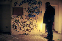 a man standing in an abandoned building covered in graffiti