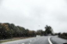 rain on a windshield and road
