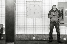 a man looking at his cellphone in a subway