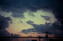 chain link fence and clouds in the sky at sunset