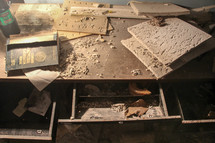 debris and ceiling tiles on a desk in an abandoned building