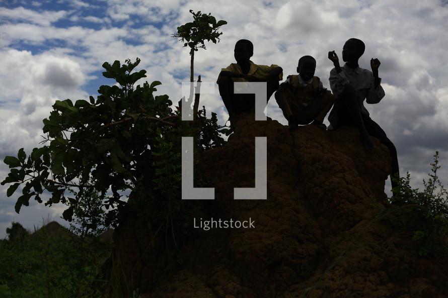 African children sitting on rock mound