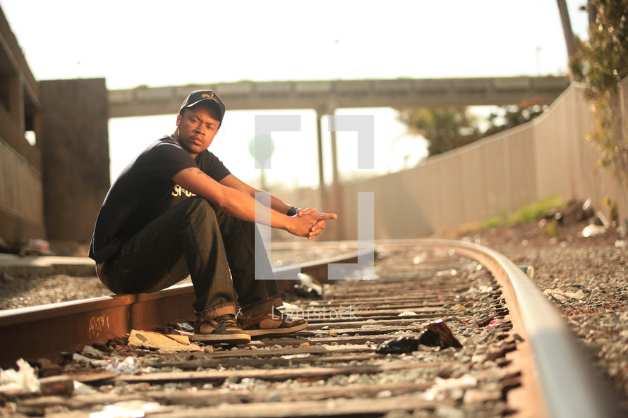 man sitting on railroad tracks